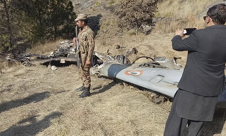 A Pakistani soldier stands guard near the wreckage of an Indian plane shot down by the Pakistan military on Wednesday, in Hurran, near the Line of Control in Pakistani Kashmir, Thursday, Feb. 28, 2019,