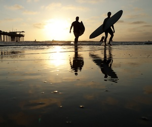 Surfers leave the water next to Scripps Pier on Aug. 2, 2018, in San Diego. The Scripps Institution of Oceanography says it has recorded the highest sea-surface temperature in San Diego in its 102 years of taking measure.