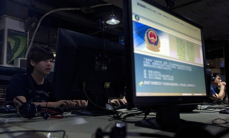 In this Aug. 19, 2013 file photo, computer users sit near a monitor display with a message from the Chinese police on the proper use of the Internet at an Internet cafe in Beijing, China.