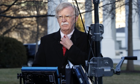 National security adviser John Bolton straightens his tie before an interview, Tuesday, March 5, 2019, at the White House in Washington.