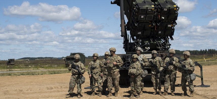 """Members of US 10th Army Air and Missile Defense Command stands next to a Patriot surface-to-air missile battery during the NATO exercise """"Tobruq Legacy 2017"""" at the Siauliai airbase near Vilnius, Lithuania, July 20, 2017."""