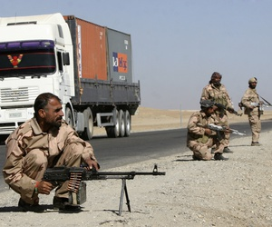 Private security contractors guard a part of a route as NATO supply trucks drive past in the province of Ghazni, south-west of Kabul, Afghanistan, Wednesday, Oct. 27, 2010.
