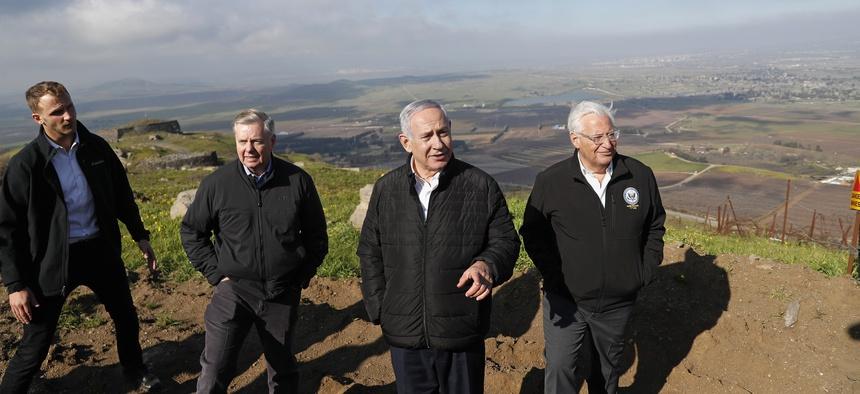 Israeli Prime Minister Benjamin Netanyahu, center, Republican U.S. Senator Lindsey Graham, second left, and U.S. Ambassador to Israel David Friedman, right, visit the border between Israel and Syria at the Israeli-held Golan Heights, March 11, 2019.