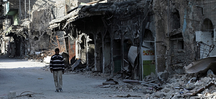 In this Friday, Dec. 29, 2017 picture, a man walks near houses and shops destroyed during the war to liberate Mosul from Islamic state militants in Mosul, Iraq.