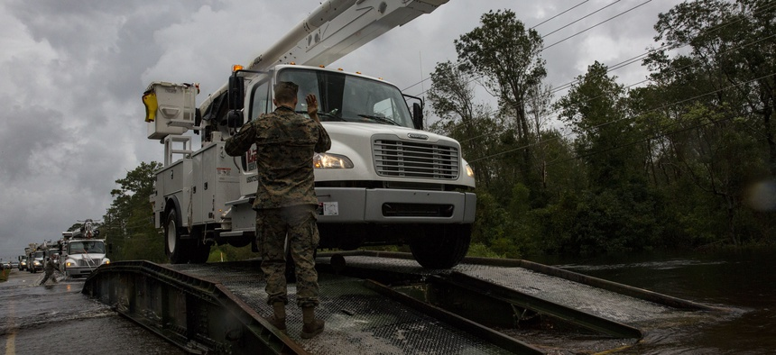 U.S. Marine Corps Cpl. Cameron D. Touchstone, left, combat engineer, directs traffic across an armored vehicle launch bridge after Hurricane Florence on Marine Corps Base Camp Lejeune, Sept. 16, 2018.