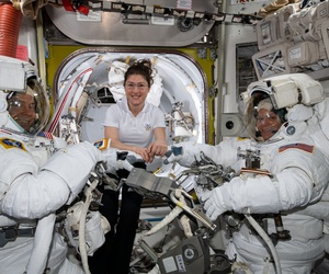 NASA astronaut Christina Koch (center) assists spacewalkers Nick Hague (left) and Anne McClain in their U.S. spacesuits shortly before they begin the first spacewalk of their careers.
