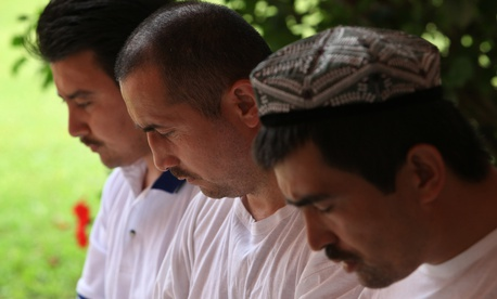 Former Guantanamo detainees pray in the courtyard of a Bermuda cottage in 2009. They are among four Chinese ethnic Uighurs who had just been released from U.S. military custody after nearly seven years in Guantanamo.