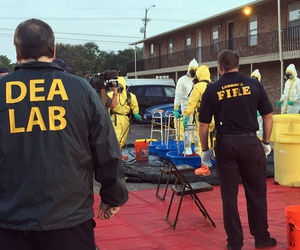 In this Oct. 27, 2016 photo, Fire Department personnel help members of the DEA Hazardous Materials/Clandestine Laboratory Enforcement Team with a decontamination procedure in Lubbock, Texas.