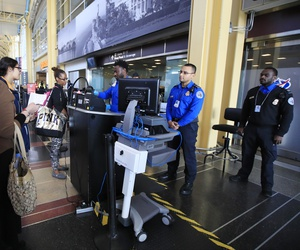 Transportation Security Administration (TSA) officers check and watch airline passengers at Reagan National Airport in Washington, Thursday, Dec. 27, 2018.