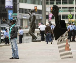 A man takes a selfie with Hank Willis Thomas' All Power to All People sculpture. The sculpture, which has a black handle topped by a clenched fist, is part of an initiative to create public works about issues such as social justice and gentrification.