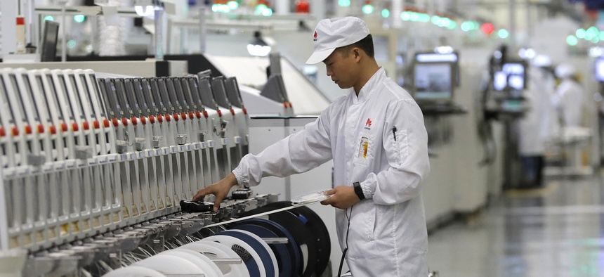 A Huawei employee works on a mobile phone production line during a media tour in Huawei factory in Dongguan, China's Guangdong province on March 6, 2019.