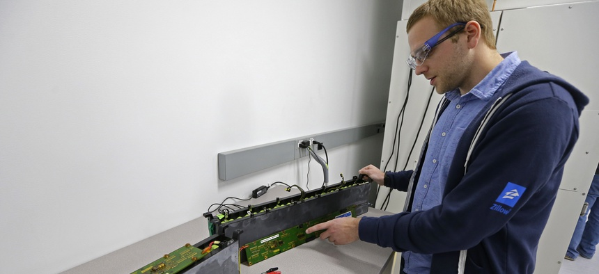 A PhD student at the University of Washington, holds a used lithium-ion battery at UW's Clean Energy Institute in Seattle, Feb. 13, 2017.