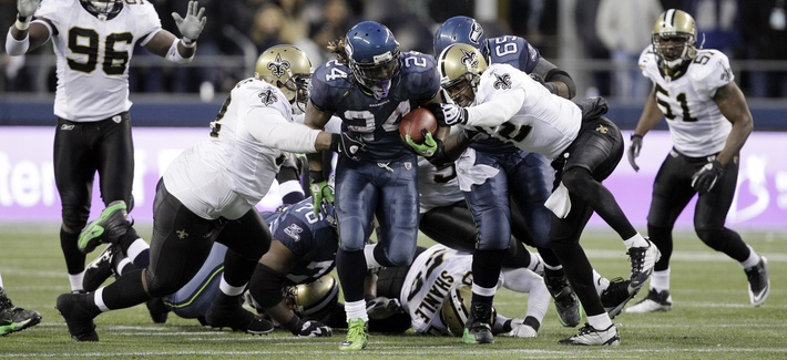 Seattle Seahawks' Marshawn Lynch (24) breaks away from a tackle by the New Orleans Saints defenders to score a touchdown on Jan. 8, 2011, in Seattle.