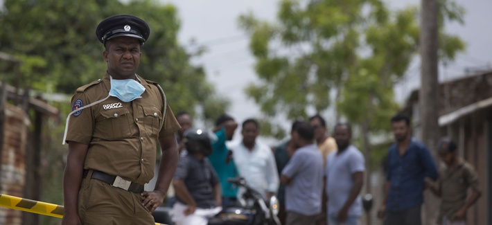 A police officer stand guards at a site of a gun battle between troops and suspected Islamist militants as neighbors gather to watch in Kalmunai, Sri Lanka, Sunday, April 28, 2019.