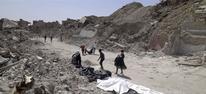 In this file image made from video taken on Monday, April 9, 2018, bodies are recovered by volunteers in Mosul's Old City.