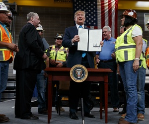 President Donald Trump holds up an executive order on energy and infrastructure after signing it at the International Union of Operating Engineers International Training and Education Center in Texas in April.