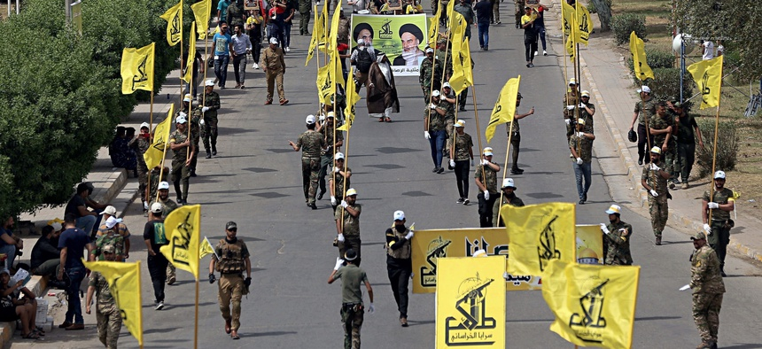 "In this June 8, 2018 file photo, Iraqi Popular Mobilization Forces march as they hold their flag and posters of Iraqi and Iranian Shiites spiritual leaders during ""al-Quds"" or Jerusalem Day, in Baghdad, Iraq."