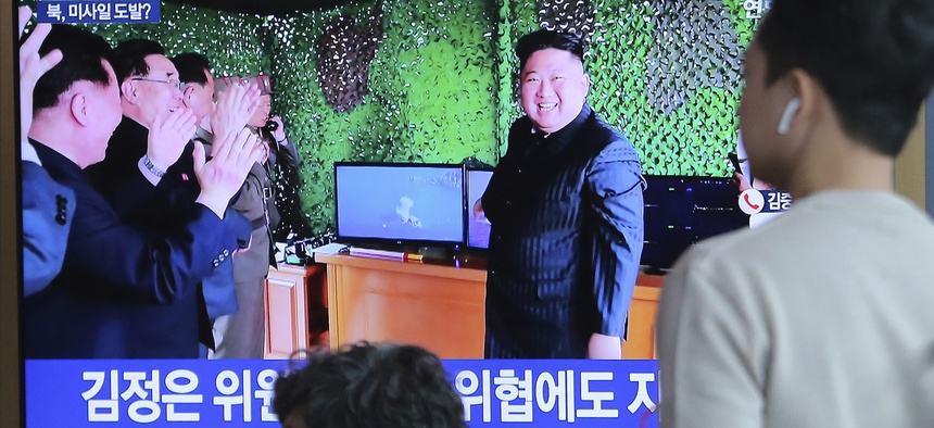 On May 5, 2019, people at a Seoul railway station watch a TV showing a photo of North Korean leader Kim Jong Un after North Korea's missile launch.