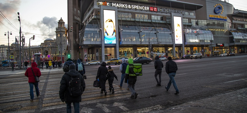 People cross the street in front of the Evropeisky shopping center, in Moscow, Russia, Wednesday, Nov. 28, 2018.