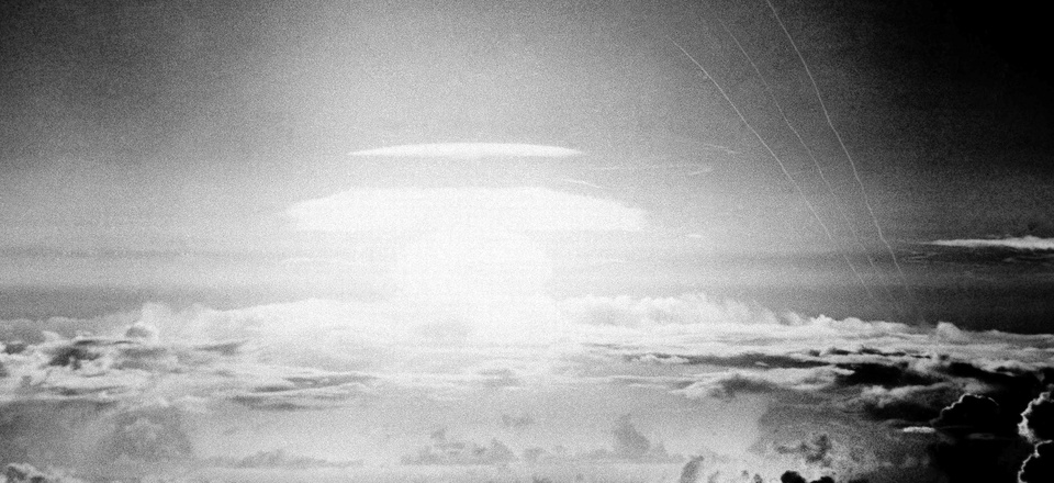 In this May 21, 1956, file photo, the fireball of a hydrogen bomb lights the Pacific sky a few seconds after the bomb was released over Bikini Atoll. Streamers at right are trails of rockets fired just before the blast for testing purposes.
