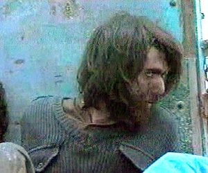 This file image taken Dec. 1, 2001, from television footage in Mazar-i-Sharif, Afghanistan, shows John Walker Lindh, right, claiming to be an American Taliban volunteer.