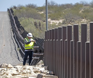 A U.S. Army Corps of Engineers employee inspects existing vehicle barrier near Columbus, New Mexico, April 11.