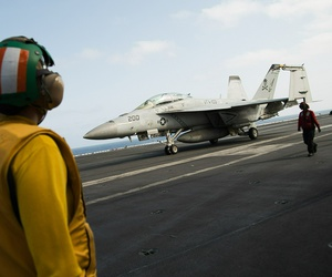 A crew member looks at a taxing F/A-18 fighter jet on the deck of the USS Abraham Lincoln aircraft carrier in the Arabian Sea, Monday, June 3, 2019.
