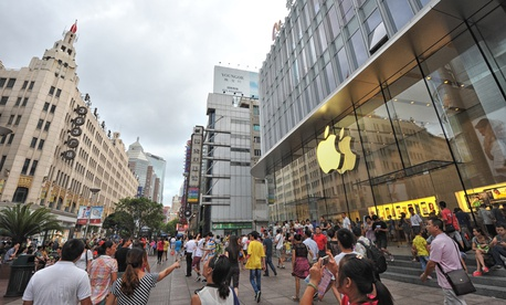 In a 2013 photo, people walk in front of the Apple store on Nanjing Road in Shanghai, China.