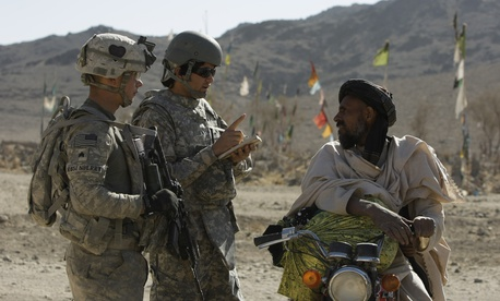 US Army Sgt. Skyler Rosenberry of Pennsylvania, left, and an Afghan interpreter, center, speak to an Afghan man during a foot patrol in Afghanistan's Kandahar province in 2010.