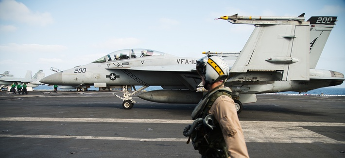 A pilot walks past an F/A-18 fighter jet on the deck of the USS Abraham Lincoln aircraft carrier in the Arabian Sea, Monday, June 3, 2019.