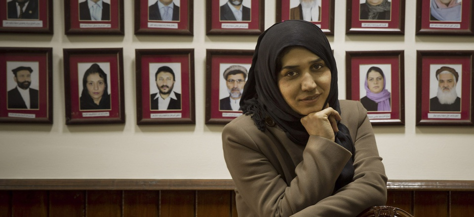 In this 2014 photo, Afghan lawmaker Habiba Danish from Takhar poses next to the picture wall showing Afghanistan's 249 parliamentarians in the parliament in Kabul.