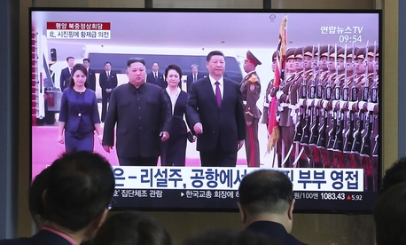 People watch a TV showing North Korean leader Kim Jong Un, second from left, welcoming Chinese President Xi Jinping at Pyongyang airport, at the Seoul Railway Station in Seoul, South Korea, Friday, June 21, 2019.