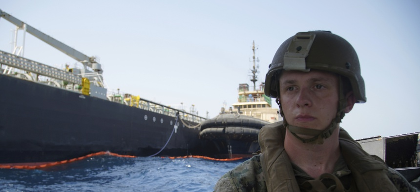 The damaged tanker Kokuka Courageous is seen behind a U.S. sailor, during a trip organized by the Navy for journalists, off Fujairah, United Arab Emirates, Wednesday, June 19, 2019.