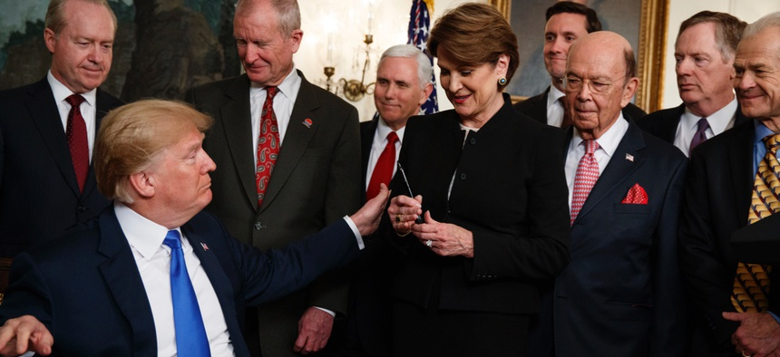 President Donald Trump hands a pen to Lockheed Martin CEO Marillyn Hewson after signing a presidential memorandum imposing tariffs and investment restrictions on China, in the Diplomatic Reception Room of the White House, Thursday, March 22, 2018.
