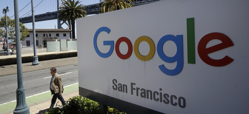 A man walks past a Google sign outside with a span of the Bay Bridge at rear in San Francisco, Wednesday, May 1, 2019.