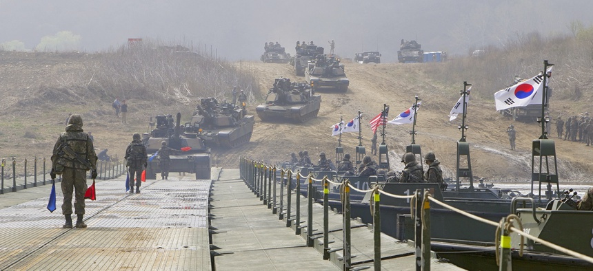 U.S. soldiers drive Abrams tanks and Bradley Infantry Fighting Vehicles across South Korea's Imjin River on a bridge assembled by Republic of Korea Army engineers in 2016.