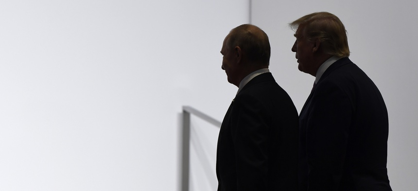 President Donald Trump and Russian President Vladimir Putin walk to participate in a group photo at the G20 summit in Osaka, Japan, Friday, June 28, 2019.
