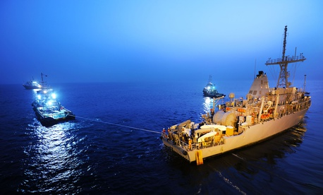 The USS Devastator, a Navy minesweeper, is pulled into position as it arrives in Bahrain in 2012.