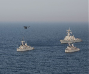 A formation of Avenger-class mine countermeasure ships USS Devastator, USS Gladiator, USS Sentry, USS Dextrous, the Arleigh Burke-class guided missile destroyer USS Mason and an MH-53E Sea Dragon helicopter during a maneuver in the Arabian Gulf July 6.