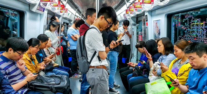 People looking at their mobile phones inside a Beijing subway train