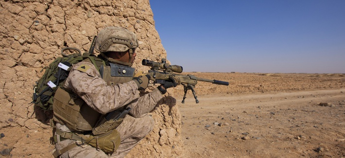 U.S. Marine Cpl. Dennis Cox, a scout sniper assigned to 1st Battalion, 9th Marine Regiment, Regional Command (Southwest), inches closer to the edge of a dirt wall during an interdiction operation in Helmand province, Afghanistan, Dec. 19, 2013.
