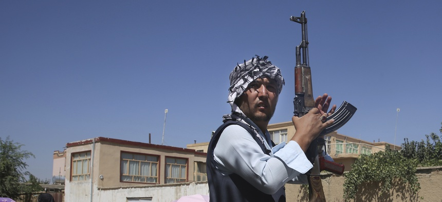 An Afghan volunteer stands guard outside a mosque during a memorial service for the victims of the Dubai City wedding hall bombing in Kabul, Afghanistan, Tuesday, Aug. 20, 2019.