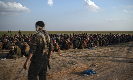 In this Feb. 22, 2019 file photo, U.S.-backed Syrian Democratic Forces (SDF) fighters stand guard next to men waiting to be screened after being evacuated out of the last territory held by Islamic State group militants, near Baghouz, eastern Syria.