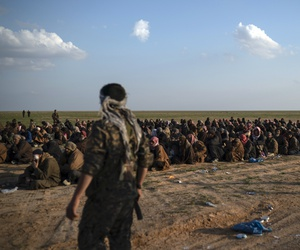 U.S.-backed Syrian Democratic Forces (SDF) fighters stand guard next to men waiting to be screened after being evacuated out of the last territory held by Islamic State group militants, near Baghouz, eastern Syria.