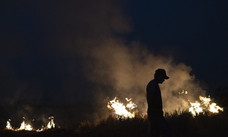 Neri dos Santos Silva, center, is silhouetted against an encroaching fire threat after he spent hours digging trenches to keep flames from spreading in the state of Mato Grosso, Brazil, Friday, Aug. 23, 2019.