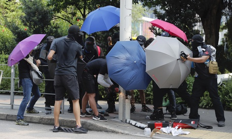 Demonstrators use umbrellas to shield themselves from view while they try to cut down a smart lamppost during a protest in Hong Kong, Saturday, Aug. 24, 2019.