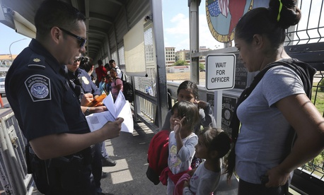 A United States Customs and Border Protection Officer checks the documents of migrants, before being taken to apply for asylum in the United States, on the International Bridge 1 in Nuevo Laredo, Mexico, Wednesday, July 17, 2019.