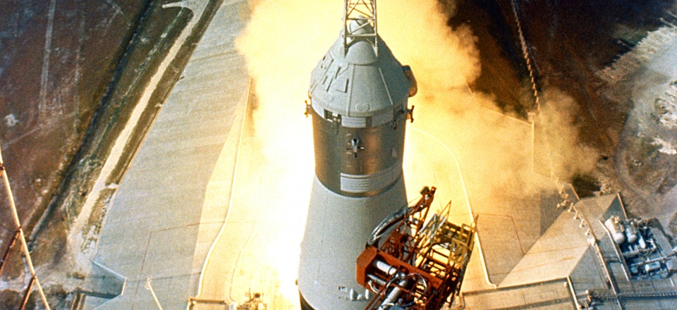 At 9:32 a.m. on July 16, 1969, the swing arms move away and a plume of flame signals the liftoff of the Apollo 11 Saturn V space vehicle.