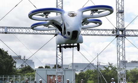 "NEC Corp.'s machine with propellers hovers at the company's facility in Abiko near Tokyo, Monday, Aug. 5, 2019. The Japanese electronics maker showed a ""flying car,"" a large drone-like machine with four propellers that hovered steadily for about a minute."