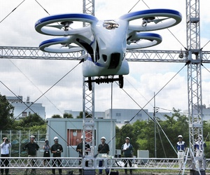 """NEC Corp.'s machine with propellers hovers at the company's facility in Abiko near Tokyo, Monday, Aug. 5, 2019. The Japanese electronics maker showed a """"flying car,"""" a large drone-like machine with four propellers that hovered steadily for about a minute."""